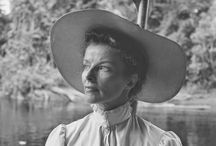 The African Queen / Katharine Hepburn, her face concealed by her massive hat, puts up her feet , Humphrey Bogart and director John Huston joined on the set by Lauren Bacall and crew members during filming of The African Queen and Katharine Hepburn adjusts her costume before a full-length mirror which was soon broken…..
