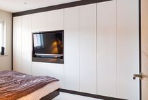 White Fitted Wardrobe / Created by bespoke furniture manufacturer Custom Creations, this white fitted wardrobe lends its contemporary aesthetic effortlessly to this bedroom. Featuring a 'cut out' area for the flat screen television, this white fitted wardrobe is framed beautifully by its mahogany skirting.