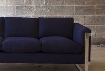 Stue / Høye gardiner. Lave bord ved veggen - får taket til å virke høyere eller?  Ulike tresorter i samme rom.  Firkantede bord med lampe på?