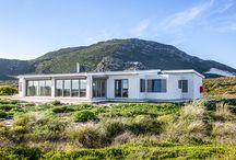Sea Farm House / Sometimes it is the landscape and sea – so close that you can taste the foam – that will linger in your memory long after you have left a special place.  Sea Farm House is set in a private nature reserve that edges Pringle Bay, with the Hangklip Mountains to its back. The house hunkers modestly down between the fynbos and dunes, architecture that gives a simple, respectful nod to the horizontal lines of sea and land. It's rather like being shipwrecked, though in luxury–a dream version of Crusoe