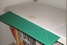 Cutting and ironing table with slots to store cutting mats