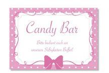 Candy Bar / Wer Süßes liebt, braucht auf der Hochzeit eine Candy Bar. Aber was ist eine Candy Bar überhaupt? Ihr nehmt einen Tisch, dekoriert diesen mit hübschen Deckchen, Tortenspitzen, Girlanden und Bonbongläsern. Dann füllt Ihr die Gläser mit Süßgkeiten Eurer Wahl. Perfekt wirkt die Candy Bar natürlich, wenn die Süßigkeiten alle farblich passend ausgewählt sind. Nostalgische Lollies oder auch Cup Cakes ergänzen die Candy Bar perfekt.
