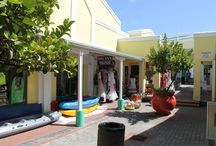 Hermanus Art & Shops / Hermanus offers a wide variety of shopping experiences. A stroll through the streets of Hermanus will lead you past second hand book stores with treasures of bygone years to the most upmarket boutiques with hip & modern stuff – simply beckoning to jump into your parcels.