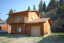 LRM Cabin / Lots of open space, perfect for parking vehicles and ATV trailers!!!  This 3 bedroom/2 bathroom 2-story cabin backs up to the mountain side. Nice open floor plan with a fireplace, free wi-fi, TV/cable, washer/dryer, charcoal BBQ grill and garage access. Walk to town and stroll main street, enjoy the shopping and restaurants. Master has a king, private balcony with access to hall bath, guest bedroom has a full bed with access to hall bath 2nd guest bedroom with twin/full bunk with bath.