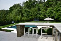 Clean Modern Lines - Pool and Spa / This NY backyard is modern and clean in it's design. With geometric shapes, white marble patio, and grey hues to the patio, it is very in style and sleek. Outdoor kitchen, bar and fireplace area incorporated into the patio area.