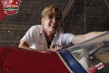 Julia Ann Wood / Piloto con más  de 17.000 horas totales de vuelo, con más de 1.500 horas de acrobacia, Julia comenzó a volar un avión a los 15 años de edad obteniendo su licencia de piloto privado a la edad de 17 años.   Comenzó su carrera de acrobacias aérea en 1996 en harvey in Aviatión en La Porte, Texas, fue allí donde conoció a su instructor y mentor Tony Wood, quién la animó a comenzar a realizar acrobacias aéreas.