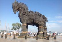 """Çanakkale Truva Atı / Truva Atı Çanakkale'de iki temsili Truva Atı bulunuyor. Bunlardan biri, Truva Antik Kenti girişinde yer alırken, diğeri ise Çanakkale sahilinde. Çanakkale sahilinde olan Truva Atı, çekimi 2004 yılında gerçekleşen, Brad Pitt'in de başrolde oynadığı """"Troy"""" adlı ünlü filmde kullanılan at. Film ekibi, film için hazırladıkları bu devasa atı Çanakkale kentine hediye etmiş. Şimdi sahilde hoş bir görüntü oluştururken, gelen ziyaretçilerinde fotoğraf karelerinde yer alıyor..."""
