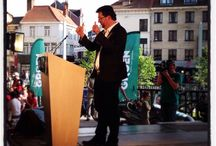 """Verkiezingsmeeting Groen (Gent, 18 mei 2014) / Groen-voorzitter Wouter Van Besien spreekt in een zonovergoten Gent een laatste keer voor de verkiezingen de leden en sympathisanten toe. """"Aan al wie nog twijfelt tussen traditioneel beleid en fris beleid, aan al wie nog twijfelt tussen stilstand en een nieuwe wind, aan al wie nog twijfelt tussen grijs en duidelijk. Aan al die mensen zeg ik: zet de stap en stem Groen in de regering."""""""