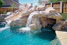 Beautiful Swimming Pool With Waterfall. / Beautiful girl swims and having fun Kids sport on family summer vacation Active holiday.