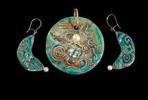 Gioielli  Raku / Moderno laboratorio,che crea oggetti in ceramica raku, un'antica tecnica giapponese risalente al XVI secolo, dove la bellezza della materia e dei caratteristici lustri metallici sono il risultato di un'alchimia che rende ogni opera unica.  Nasce da una molteplicità di elementi la fortunosa e casuale combinazione di terra, aria, acqua e fuoco. La ricerca formale è ispirata a modelli e visioni etniche e ancestrali. L'obbiettivo, è quello di creare delle forme senza tempo...