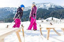 Bildstarker Schneespaß mit Kindern / Schneeweiß und leuchtende Farben in einem klaren Layout. Mit dem Schlitten fahren, Schneebälle werfen, auf den Skiern unterwegs und einen Schneemann bauen.