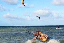Kite Surf / Le kitesurf est un sport de glisse consistant à évoluer avec une planche à la surface d'une étendue d'eau en étant tracté par un cerf-volant (kite en anglais) spécialement adapté, nommé aile ou voile.  Le kitesurfeur accroché à l'aile par son harnais est piloté à l'aide d'une barre où sont reliées les lignes de traction. Il est soumis dans son mode de déplacement aux lois physiques de la navigation à voile.
