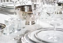 """Silver Soiree / Charger Plates 13"""" ROUND PLATINUM BAND CHARGER - GLASS  Plates: VERSAILLES  PLATE  Flatware KING JAMES CUTLERY  Glassware: Westmount Platinum CHAMPAGNE SAUCER  Linen: CONFFETI 102""""x156"""" WINTER WHITE Beverley Hills Satin Napkins Candlelight  Platters & Bowls SILVER REVERE BOWL   Seating BLANC CHATEAU CHAIR  Votives ICE CUBE VOTIVE WITH TEA LIGHT"""