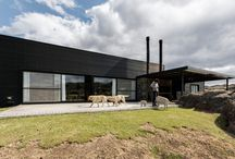 Acero Negro / Bajo un contraste de colores cálidos podemos apreciar una vivienda modular de color negro.