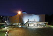 Hegel-Saal / Der Hegel-Saal ist der zweitgrößte Raum im Kongresszentrum und bietet fast 1.900 Besuchern Platz. Er steht im Mittelpunkt eines variantenreichen Raum-Ensembles. Seine Grundfläche bildet ein Siebeneck, eine siebeneckige Glaskuppel krönt diesen einzigartigen Saal. Imposant herabhängende Glassegel sind weit mehr als ästhetische Artefakte, sie sind wichtige Komponenten des durchdachten Schallsystems, das für die gute Akustik sorgt.