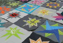 """Shades of Gray + a POP of color Star Block Lottery / 2nd Block Lottery for ECMQG.  Made by members of ECMQG.  Block size = 12.5"""".  Any star block could be used, ideally with modern fabrics."""