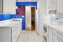 NFC Portfolio: Sleek Petite / This sleek petite kitchen features Columbia high gloss laminate cabinets with a grey acrylic edge. Stainless steel hardware, and white appliances continue the modern European aesthetic. Cobalt blue walls and a hand-blown artistic glass pendant brighten this petite space.