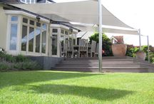 Shade Sails / Rain & Shade Sails / Shade & Rain sails are an alternative solution to awnings, to have either in a home or work place. They create not just shade from harmful UV light but also offer unique and authentic patio, atrium or sheltered features. Creating an enjoyable alfresco ambience for all to enjoy. Using high tech PVC  fabrics with correct design we create Rain & Shade sails maximising your Alfresco time.