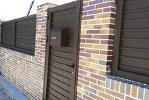 Cerramiento ladrillo visto / Cerramiento de parcela con ladrillo visto y carpintería marrón. Esta combinación es muy decorativa por su contraste, y el buzón encastrado en el portón muy útil y discreto.
