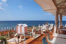 Marinelli Bagni - Beach Club / Tra i colori e i profumi tipici della macchia mediterranea, Marinelli Bagni è uno stabilimento balneare chic, sofisticato ed elegante dall'atmosfera retrò, perfetto per i turisti che amano scoprire gli angoli segreti del Salento, con le sue calette poco affollate e i luoghi immersi nella natura. Un luogo aperto dalla mattina alla sera, in cui rifugiarsi dal caos delle spiagge affollate e dallo stress di tutti i giorni.