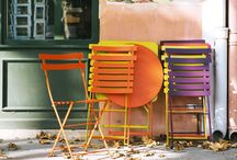 Outdoor Furniture - Fermob - Bistro range / FERMOB - BISTRO RANGE  The very popular Bistro folding chair made in France by Fermob is perfect for  entertaining. It creats a wonderful ambience in any environment, be it a small space, balcony or large rambling garden.   Add to it a very charming and versatile Bistro table which folds flat and is made of lacquered steel. They can be found in a variety of shapes and sizes.   The Bistro range is available in 23 fabulous Fermob colours.