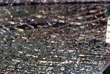 Crackle Glass / The wonderfully reflective properties of crackle glass transforms small areas and brings individuality to bigger ones. Our Crackle Glass is made by laminating 3 pieces together with only the middle piece being toughened. The toughened piece is then shattered leaving the cracked ice effect permanently captured and sealed within the outer glass layers. Available in clear, mirrored or coloured finishes and with a seamless grout-free look, crackle glass makes an impressive focal point for any room.