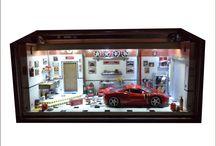 Diorama Oficina Ferrari 458 Italia / 44 L x 20 P x 21.5 H em mdf encerado com carnaúba, iluminação com 3 interruptores, leds brancos para acionamento lado direito e esquerdo, e azuis na parte superior do fundo, 110/220v. Escala 1/24, peças de plastimodelismo, recicladas de aparelhos eletrônicos, relógios, bijuterias, madeira balsa, biscuit . Criação e impressão digital para quadros, papel de parede, livros, jornal, rótulos e piso, fazem parte da elaboração interna. Vidro superior articulado e frontal removível.