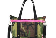 The ANDI / Our Signature ANDI is designed and crafted to be an ideal carrying companion for the plane, the weekend or a full day with necessary accoutrements. It is sized to fit a laptop computer + change of shoes and clothes + additional accessories. The remarkable and ironic appeal of camouflage with fluorescent pink empowers the Large Camo ANDI to pair across the color wheel and lend enchantment to every occasion.