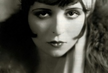 flapper / 1920s beauty: -- Face: pale, rounded, delicate, little definition, rouged cheeks -- Eyebrows: low, straight or gently curved, thin, defined -- Eyes: dark, defined, rimmed -- Lips: small, exaggerated cupid's bow, dark -- Hair: bobbed, deeply sideparted, usually curly or wavy, soft, flirtatious -- Figure: slim, boyish / by erinne elise