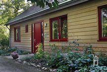 Scanabouw Houtskeletbouw / Een huis met een puntdak. We wilden per sé houtskeletbouw. Zo kwamen we bij ScanaBouw. We hadden wel een eigen schets onder de arm en toen bleek pas hoe flexibel ScanaBouw is en ook hoeveel ervaring zij met houten woningen hebben!  Red cedar buitenkant.  De woning heeft een mooie doorsteek van lichte entree bij de voordeur naar licht bij de achteringang/uitgang. Verder is er meteen een forse serre op de zon geïntegreerd.
