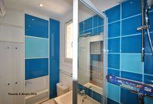 Petite salle de bain avec laque bleue / Assorties au carrelage de la salle d'eau les portes de ce petit rangement haut et peu profond se fondent complètement dans les murs