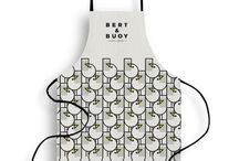APRONS / Good cook? Bad cook? No-one will care when you're wearing a Bert & Buoy apron. Heavy natural cotton with Bert's beautiful coastal illustrations applied. Keep them, gift them, shop them now.