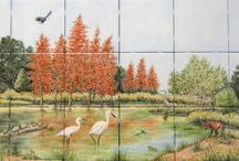 """""""Louisiana Snowy Egrets & Bald Cypress"""" kitchen backsplash tile mural / Louisiana swamp scene featuring snowy egrets and bald cypress. Shown in painting are male and female snowy egrets, red fox, bald eagle, great blue heron, bullfrogs, sunning turtles on log and striking coppery-red bald cypress in typical scenery, vegetation and wild life found in a Louisiana swamp. Custom designed, hand painted, kiln fired ceramic tile mural for kitchen backsplash. Design based on collaboration between homeowner/client, designer and artist Julia Sweda."""