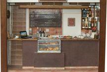 Cafeteria NO CAFÉ - Personalizado / Tamanho: 24L x 12P x 22H Diorama laborado em MDF e acabamento branco. Peças recicladas, madeira balsa, bijuterias, miniaturas de objetos, garrafas e copos, tecidos, criação e desenvolvimento para impressões de azulejos, quadros, revistas, capas de livros, fotos, rótulos dos produtos e bebidas, papel de parede, espelho, acrilico, transparência e biscuit,  fazem parte do contexto interno com uso de vidro frontal embutido. Obs. Réplica exata do ambiente, balcão e serviços.