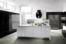 Penthouse View / Like the city beyond its windows, this kitchen is sleek and lively. Black gloss cabinets span the room's perimeter while the white island and gray armoire create contrast and warmth.