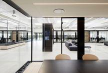RAVN_Domicil M / Kontoret er indrettet i  ét stort rum på knap 1.000m2, hvor fritstående mødebokse definerer opholds- og arbejdszoner. Indgangen er placeret centralt i rummet og inddeler således rummet i et storrumskontor til medarbejderne og et præsentations- og loungeområde til kundebesøg.