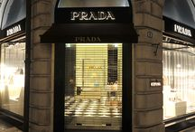 Windows and Doors PRADA - Padova, ITALY / Black painted iron, with frame polished stainless steel insert, led backlit plexiglass signs, safety extra clear glass coupled 8+8.