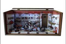 Diorama Oficina moto Yamaha MT 09 - Customizada Motors Company / Tam 44 Lx 20 P x 21.5 H. Em mdf encerado com carnaúba, iluminação por leds, interruptor e fonte 110/220. Carro escala 1/18 e elaborado com peças novas de plastimodelismo e recicladas de aparelhos eletrônicos, tv, som, relógios, bijuterias, madeira balsa, biscuit, com caixa de ferramentas com tampa para mensagem pessoal. Criação e impressão digital para quadros, papel de parede, livros, jornal, rótulos e piso, fazem parte da elaboração interna. Vidro superior articulado e frontal removível.