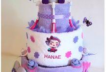 Mes gâteaux de couches / Cadeau de naissance composé de couches et de divers accessoires pour bébé, tout cela présenté sous forme de gâteau.
