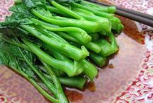 Best Recipes Using Gai Lan / Asian Broccoli Rapini, aka Chinese broccoli or Chinese kale.  The stalks taste similar to broccoli, while the leaves taste like greens. Some say it tastes like a cross between broccoli, kale and Swiss chard. Long leafy stalks topped by little green flower heads and sometimes a few white flowers, eaten either raw or cooked -- the whole thing is edible. Try it!