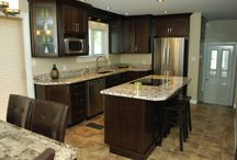 Dark wood cabinets..a quaint but pratical kitchen / Custom made kitchen with island. Dark painted wood doors with a vibrant granite counter top.