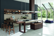 Arts and Crafts Kitchen Range by Pedini London /  Designed to blend seamlessly into the popular open plan lifestyle, Arts and Crafts unites kitchen & living spaces by offering a selection of free standing, & wall mounted modular units.  Available in a number of new finishes, including stylish Canaletto walnut, with pewter highlights & smoked grey glass.   A wide range of cabinetry is available including statement feature wall units with deep 110mm glass box doors, leather strap hinges  & integrated LED lighting.