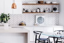 Kitchen / Polished concrete floor White bench top White Island bench Wooden look shelving on end of island bench White or light grey glass splash back Higher bench on other end of island  Wooden laminate cupboards on back wall  Cut out handles or no handles  Lights over bench top