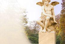 Grabengel / Ein aus Stein gehauener Engel steht für ein Gefühl von Verbundenheit und Schutz, das besonders in der schweren Zeit der Trauer Trost und Hoffnung spenden kann. In ihrer Würde strahlen sie etwas Beruhigendes und Sanftes aus. Schutzengel waren schon immer ein Symbol der Spiritualität. Sie sind wie eine Brücke zwischen Himmel und Erde.