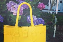 Model M. - CITRINE (yellow) / She's not just the 'it' bag of the season, she's a modern classic.  Fabricated of Fashion-Flex™—a proprietary polymer—Model M. withstands any fashion forecast. Model M. is stylish, resilient, light-weight, and patent-pending. The easy-to-wear construction gives the handbag a sculptural silhouette that never slouches. In seven vivid colors—Emerald, Onyx, Tourmaline, Citrine, Diamond, Topaz and Aquamarine—Model M. is a head-turner, just like you.