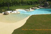 Modelo Almaro de Piscinas de Arena / Aparte de crear un diseño único y exclusivo para cada Piscina de Arena también te damos ejemplos como el modelo Almaro, ahora con dos playas y banco de burbujas. Cotas de la piscina (14x6m) Superficie laminar de agua: 33m² (10x4m) Superficie paredes y fondo: 70m².  Superficie de playa: 26m². Volumen de agua: 28m³. Profundidad máxima: 1,6.m. Uso piscina: Privada. Tipo piscina: Descubierta. Vaso piscina: Hormigón gunitado. Conexión Eléctrica: monofásica. Revestimiento: Arena compactada NaturSand®
