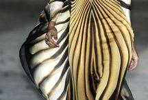 Tropicalismo Étnico | MACROTENDÊCIA / A cor verde bandeira será forte e também de animal print com folhagens. Índios estilizados, tricô com pontos mais abertos como se representassem redes, materiais que remetam aos animais silvestres, estampas que imitem a madeira nas roupas a exemplo do que é feito com os materiais usados na decoração. Amarrações para sandálias e rasteiras, tear, tranças. Fortes referências de elegância da moda africana, mais especificamente do Quênia.
