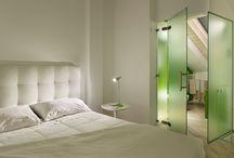 Suite Moderna / Una tela bianca con pennellate di colori accesi nei quali spicca un dominante verdemela per un ambiente luminoso, con una vista mozzafiato sul paese dipinto e sul solarium dell'agriturismo.