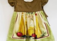 Oven Door Dresses / Our one of a kind Oven Door Dresses are here! They hang over your oven door handles. Our styles come and go quickly, so check out our website to see what is in stock now. Designed and made in the USA by The Bib Shoppe.   www.bibshoppe.com