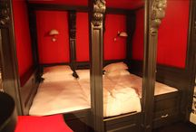 The Red Room at The Hollies / This compact room is a sumptuous room decorated in Shot taffeta curtains with an eight poster bed which can be made up and an extravagant 9′ bed or a twin. The Grand Mirrored bathroom is just over the hall.